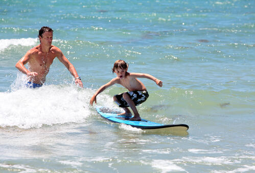 father and son surfing on sunny day