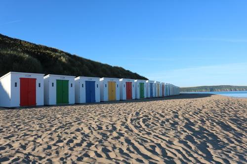 multi-coloured beach huts along woolacombe beach on blue sunny day