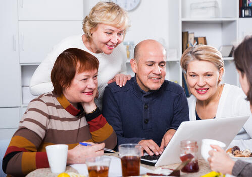 friends gather round laptop to organise a staycation