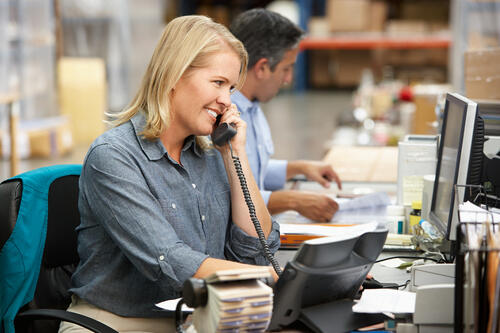 Business woman answers phone at desk