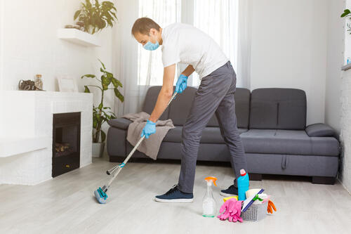 professional cleaner mops floor wearing PPE