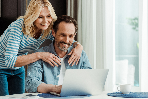 middle aged couple use laptop