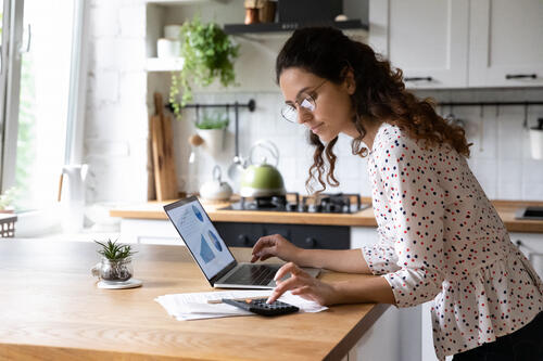 woman calculates finances at kitchen table