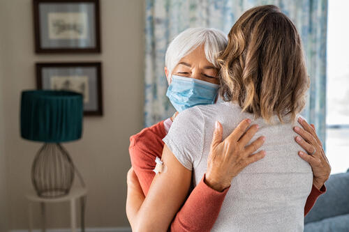 elderly woman wearing face mask hugs daughter after her COVID-19 vaccination