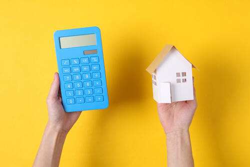 hands hold a calculator and model house on yellow background