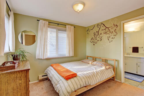 bright bedroom with green walls and striped bedding