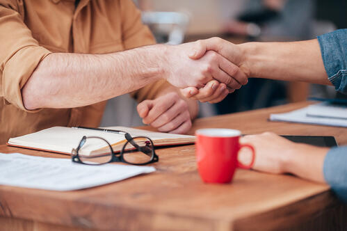 two men shake hands over business deal