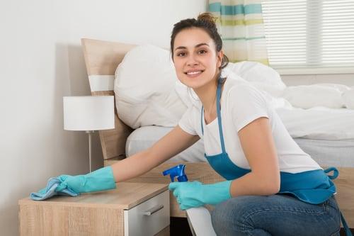 happy female housekeeper cleaning nightstand in bedroom