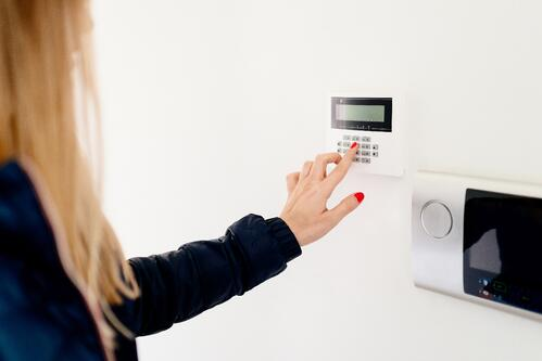 woman enters code to house security system