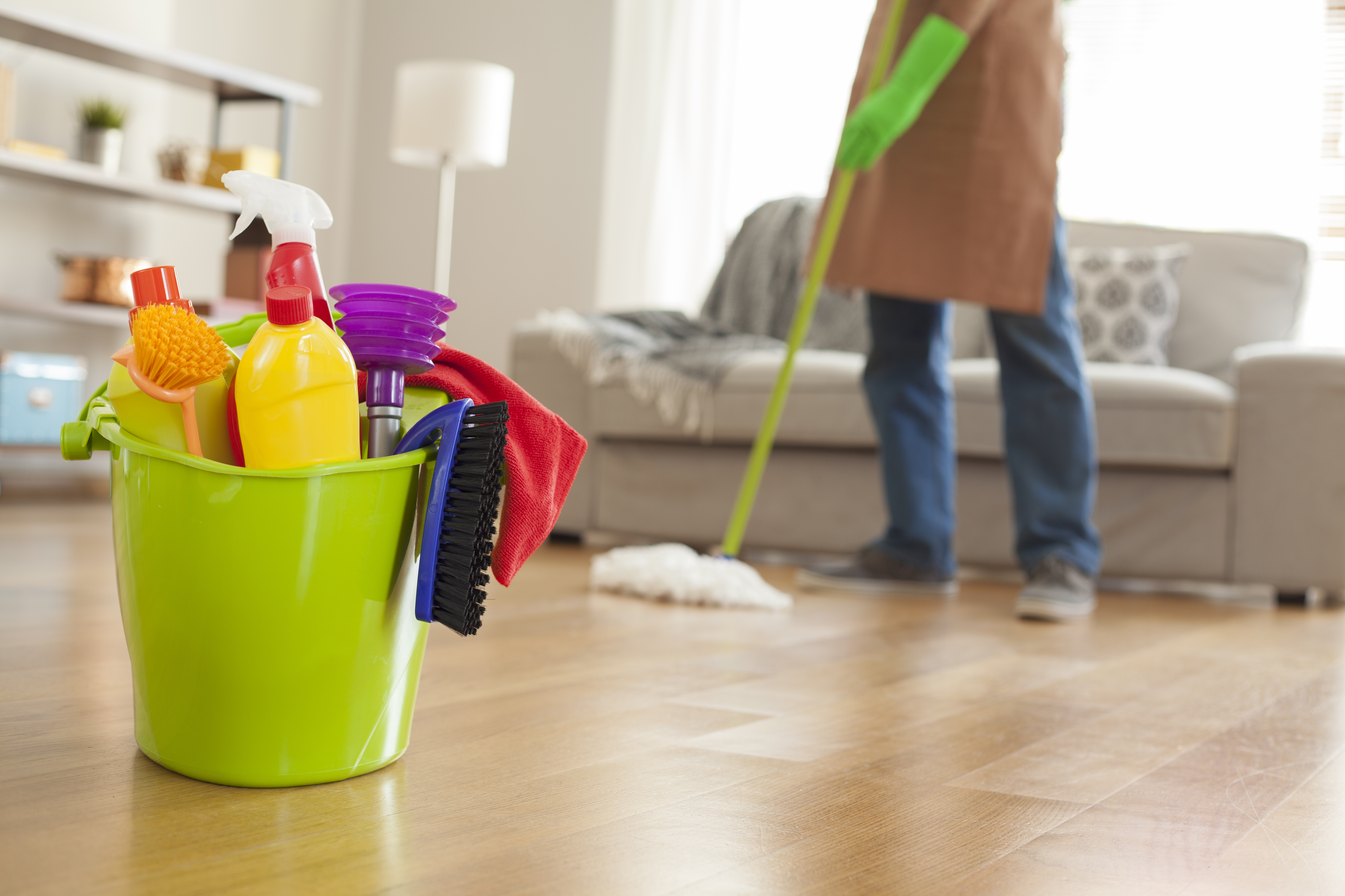 man mopping floor with cleaning supplies in focus